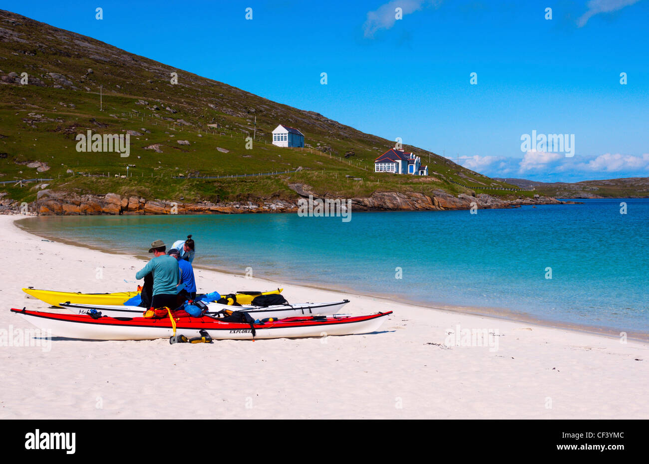 Kayakers preparing their equipment on a beach on the island of Vatersay in the Outer Hebrides. Stock Photo