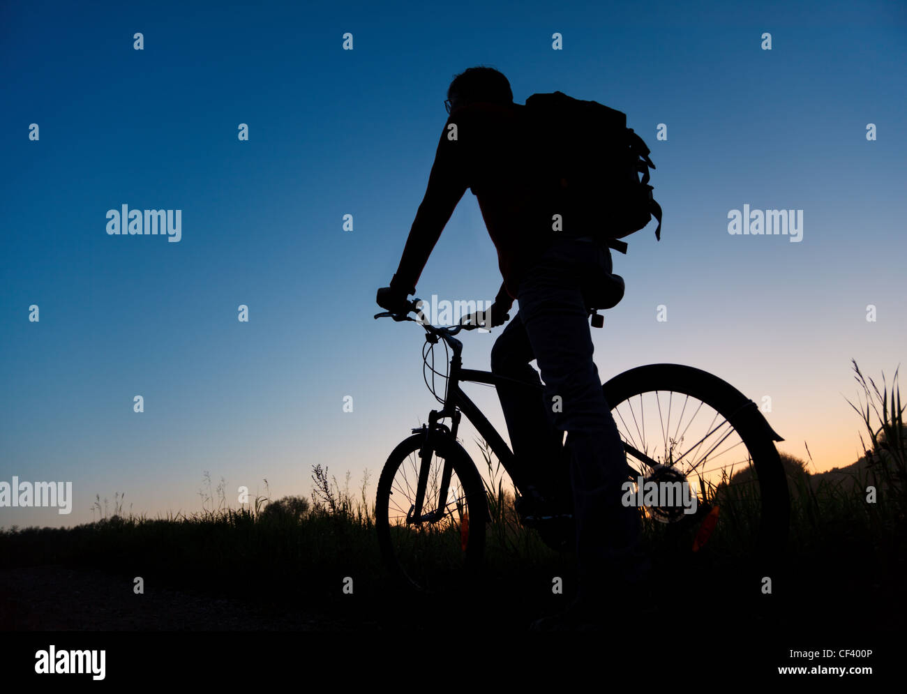 Silhouette of the bicyclist against the dark sky - Stock Image