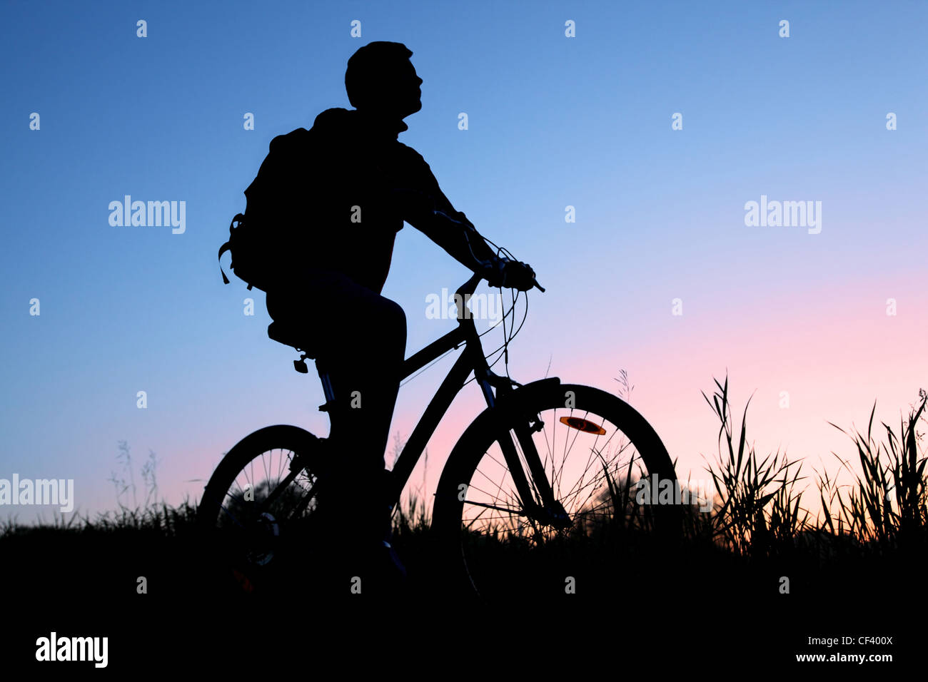 Silhouette of the bicyclist against the sunset sky - Stock Image
