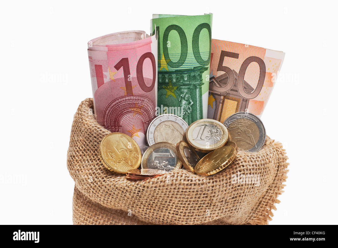 Viele Euro Banknoten und Münzen befinden sich in einem Jutesack.   Many Euro bills and coins in a jute bag, - Stock Image