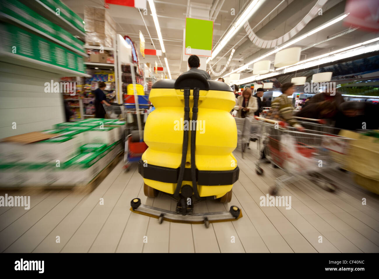 Motion blur of yellow clean machine in centre of trading floor in supermarket - Stock Image