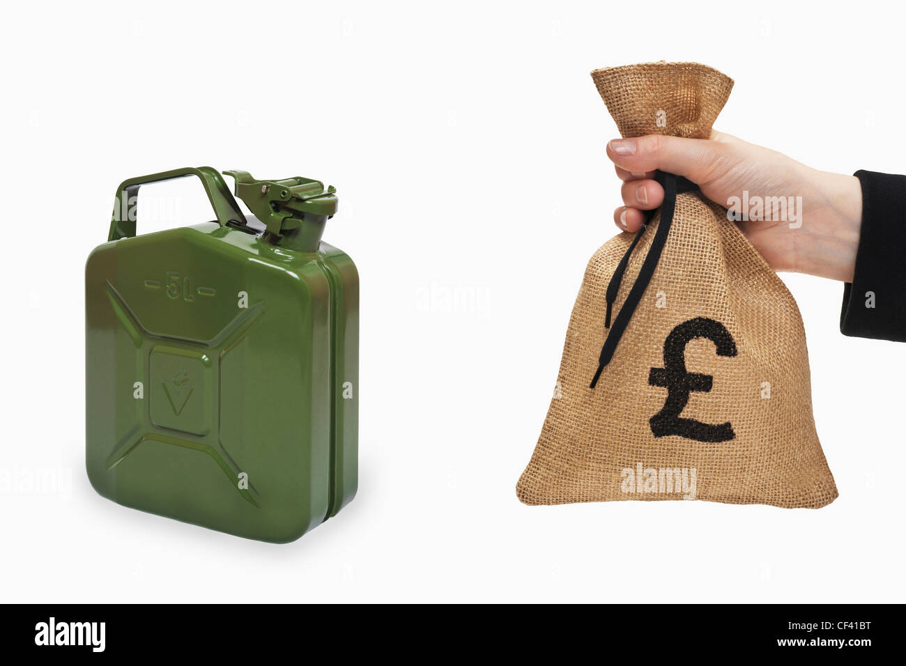 A money bag with a Pound currency sign is held in the hand. Near by is a green 5 liters gasoline canister of metal. - Stock Image