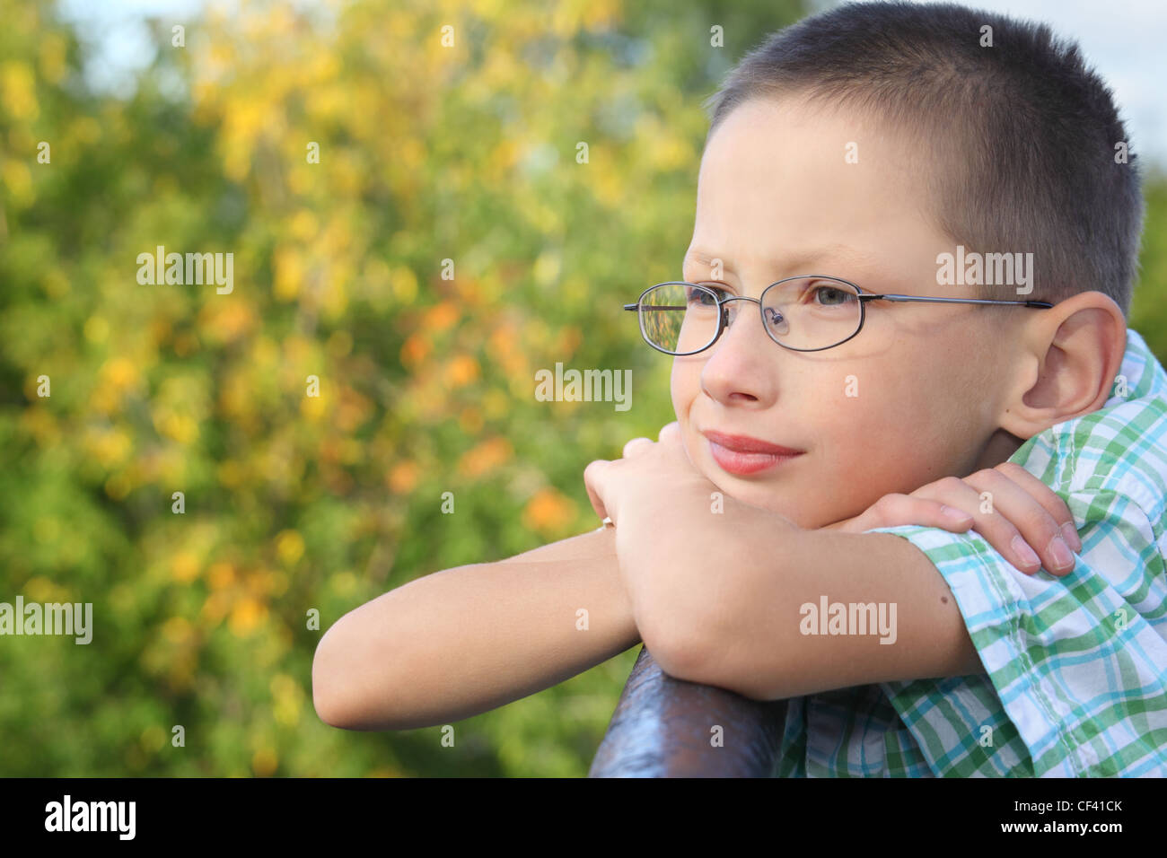 little boy is lean elbow on bridge fence and looking forward - Stock Image