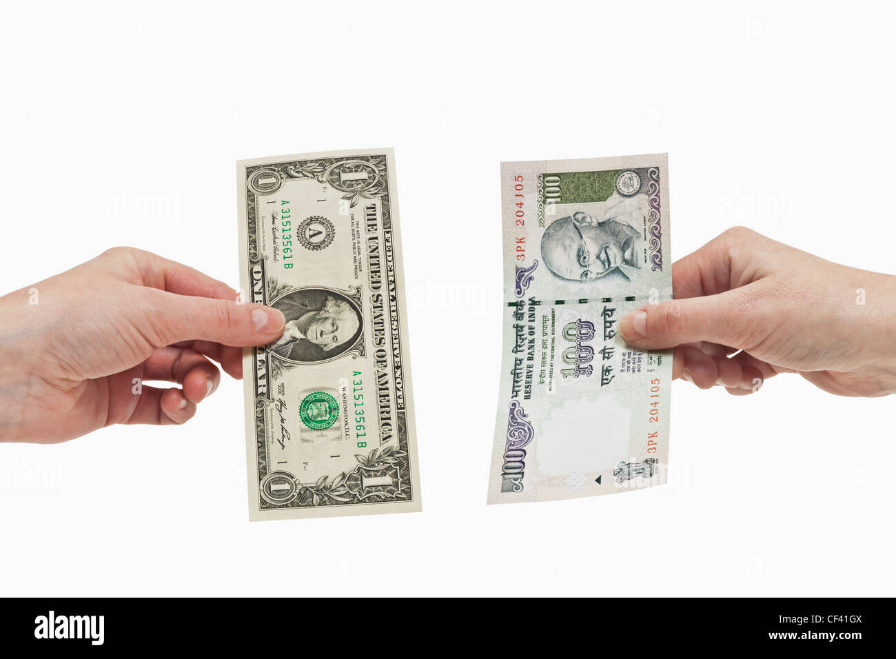 One 1 U.S. Dollar bill is held in the hand. At the other side a Indian 100 rupees bill is held in the hand, background - Stock Image