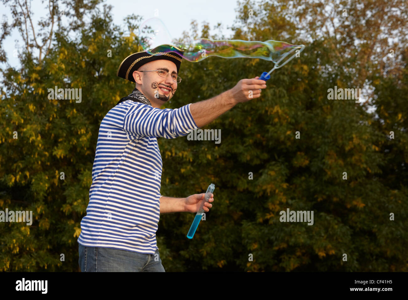 joyful man with drawed beard and whiskers in pirate suit is blowing soap bubbles. - Stock Image