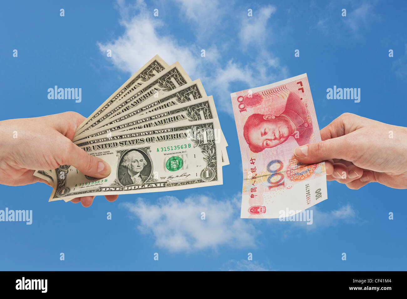 Five 1 U.S. Dollar bills are held in the hand. At the other side a 100 yuan bill is held in the hand, background - Stock Image