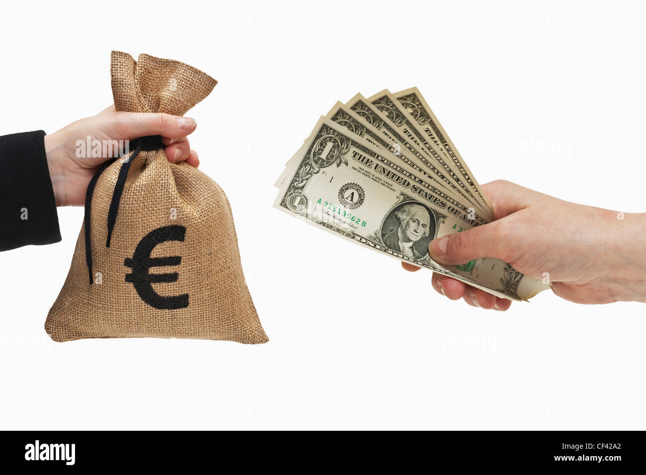 Five 1 U.S. Dollar bills are held in the hand. At the other side a money bag with Euro currency sign held in the - Stock Image