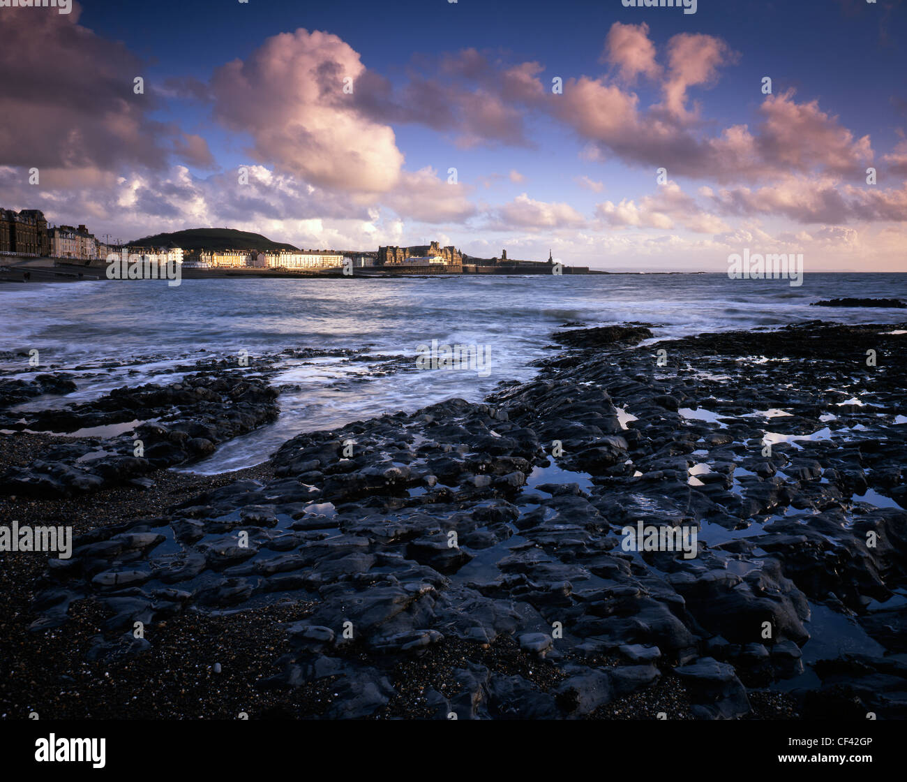Looking across Cardigan Bay towards Aberytswyth's Victorian promenade. - Stock Image