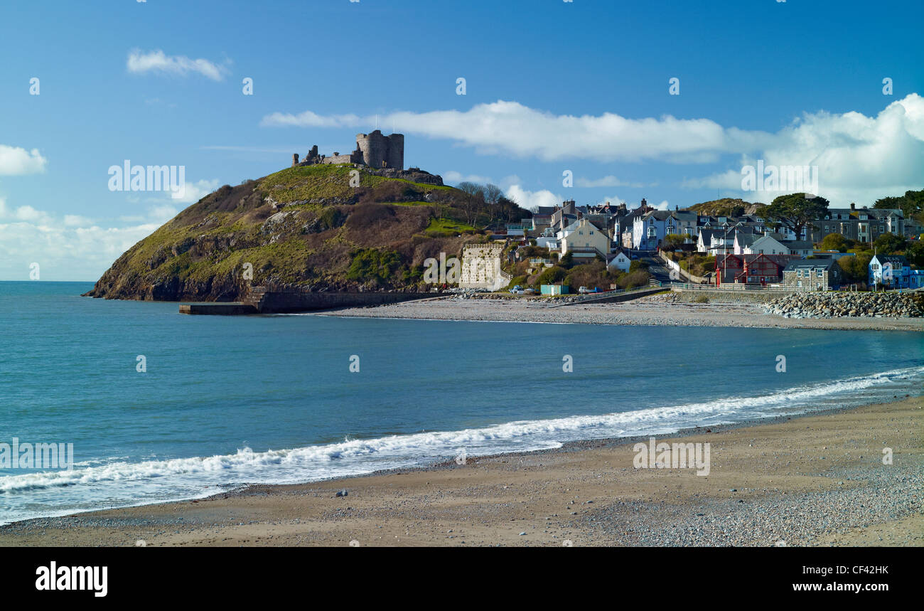 View across a deserted beach towards the ruin of Criccieth castle towering over Tremadog Bay. - Stock Image