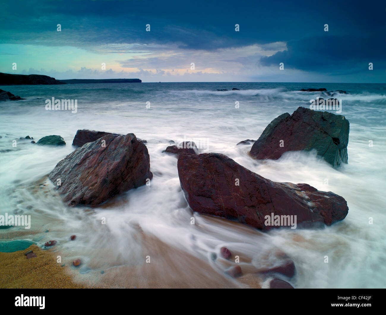 Waves roll onto the beach around large boulders at Freshwater West during high tide. - Stock Image