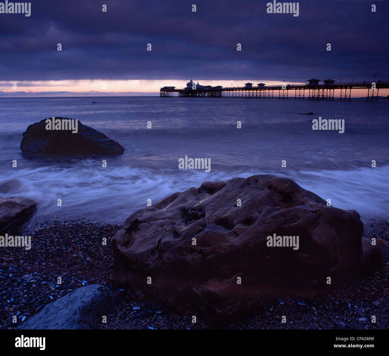 View over large boulders on the seashore towards Llandudno Pier at dusk. - Stock Image