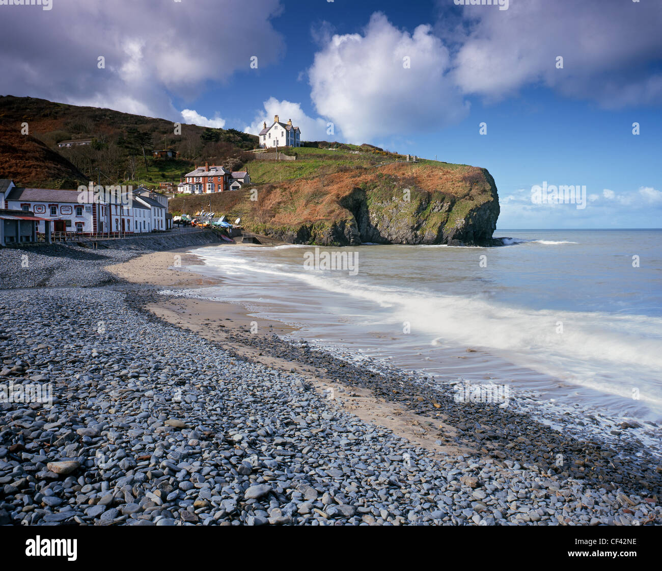 The pebbled beach on the seafront at Llangrannog. - Stock Image