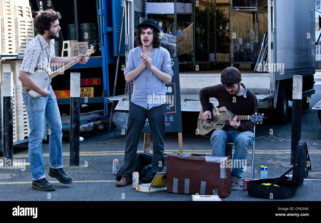 A trio of buskers, Columbia Road Market, London, England, UK - Stock Image