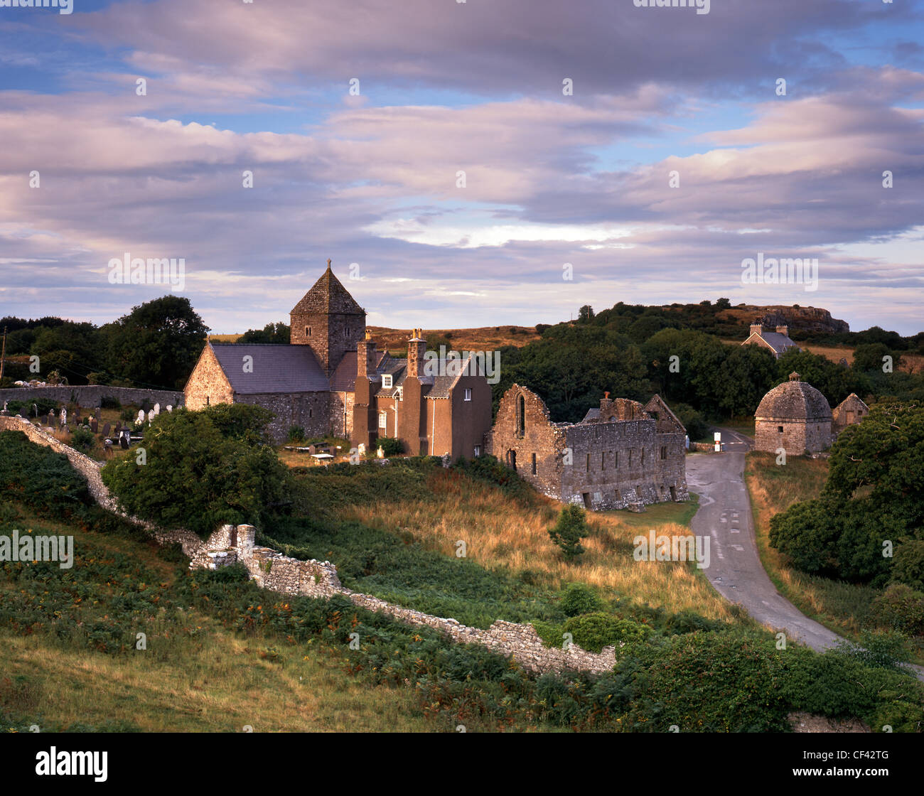 Fading sunlight illuminates the remains on Penmon Priory and Priory church which serves as the parish church today. - Stock Image