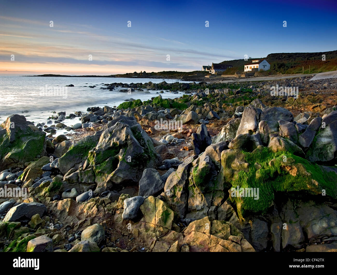 Dawn breaks over the rugged coast at Port Eynon on the Gower Peninsula. - Stock Image