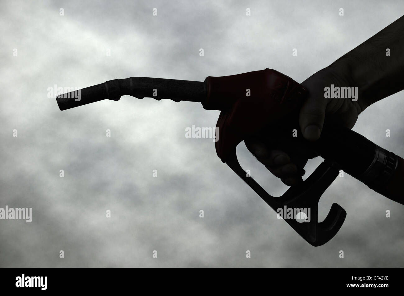 Hand Holding a Petrol Pump Nozzle Silhouetted Against a Dark Cloudy Sky. - Stock Image