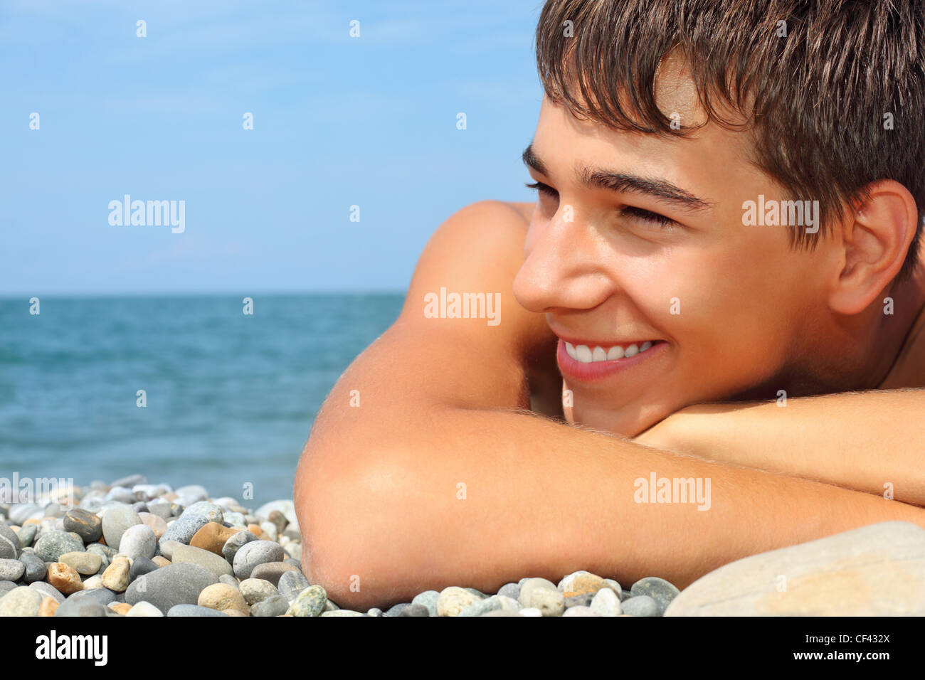 teenager boy lying on stony seacoast, looking afar - Stock Image