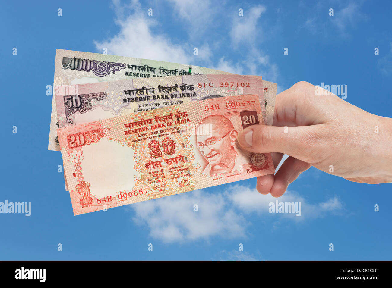 One 20. one 50 and one 100 Indian rupee bills with the portrait of Mahatma Gandhi are held in the hand. Sky is in - Stock Image