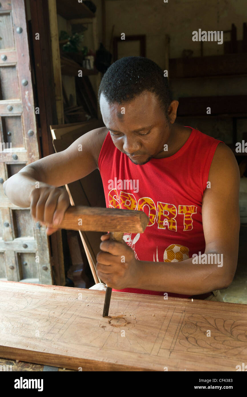 Carpenter carving an ornate frame for a bed Stone Town Zanzibar Tanzania - Stock Image