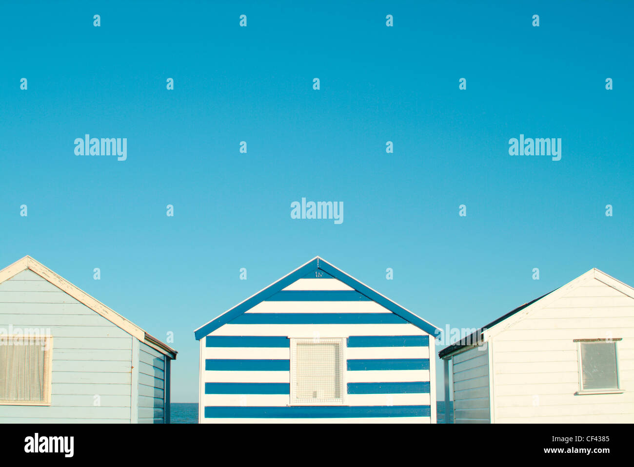 Colourful beach huts. There is something quintessentially British about sitting outside what is essentially, a shed, - Stock Image