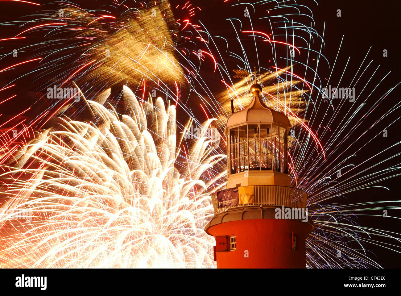 Fireworks exploding behind Smeatons Tower lighthouse on Plymouth Hoe. - Stock Image