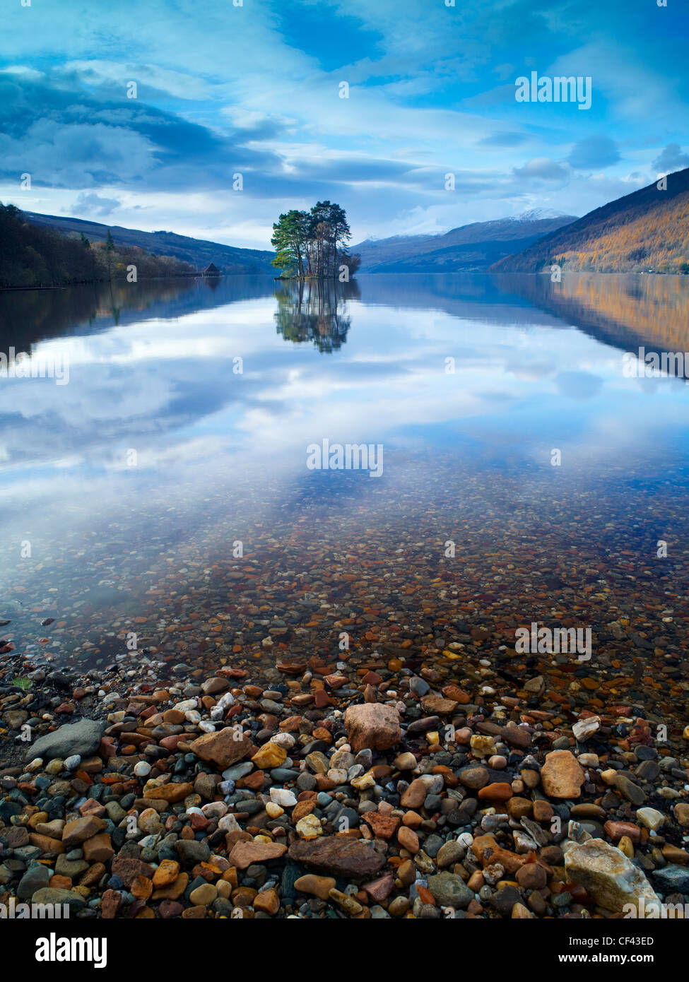 The sky and surrounding hillside reflected in the still waters of Loch Tay on a winter morning. - Stock Image