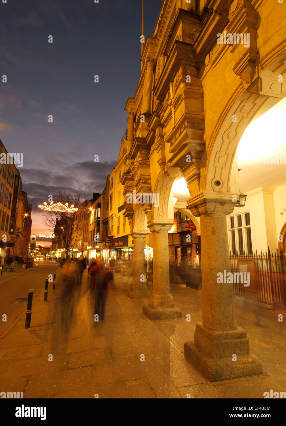 Christmas shoppers rushing past the Guildhall on Exeter High Street at dusk. - Stock Image