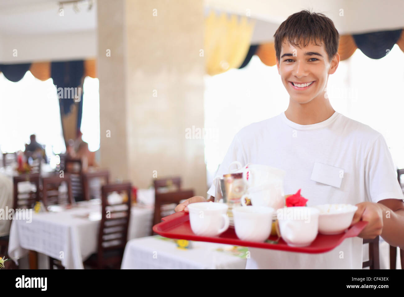 young smiling affable waiter keeps tray with dishes at restaurant, wide angle - Stock Image
