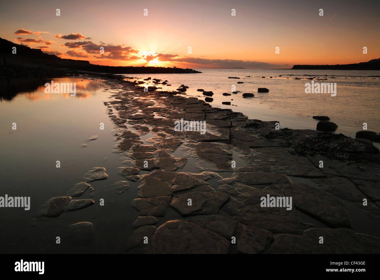 Vivid sunset over the Jurassic Coast at Kimmeridge Bay lighting up the jigsaw shaped prehistoric rock beds. - Stock Image
