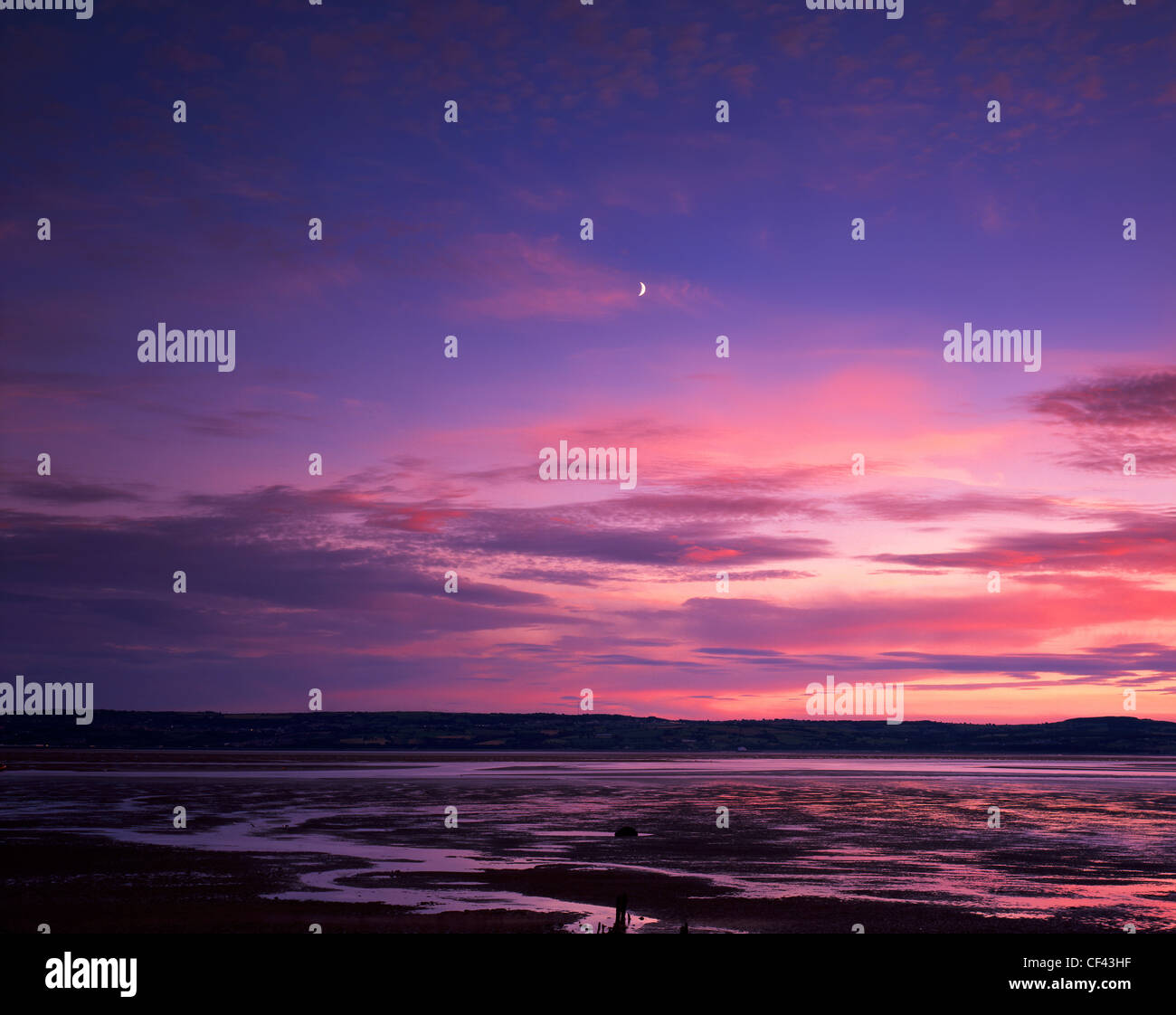 A crescent moon over the Dee Estuary looking towards north Wales from the Wirral peninsula. Stock Photo