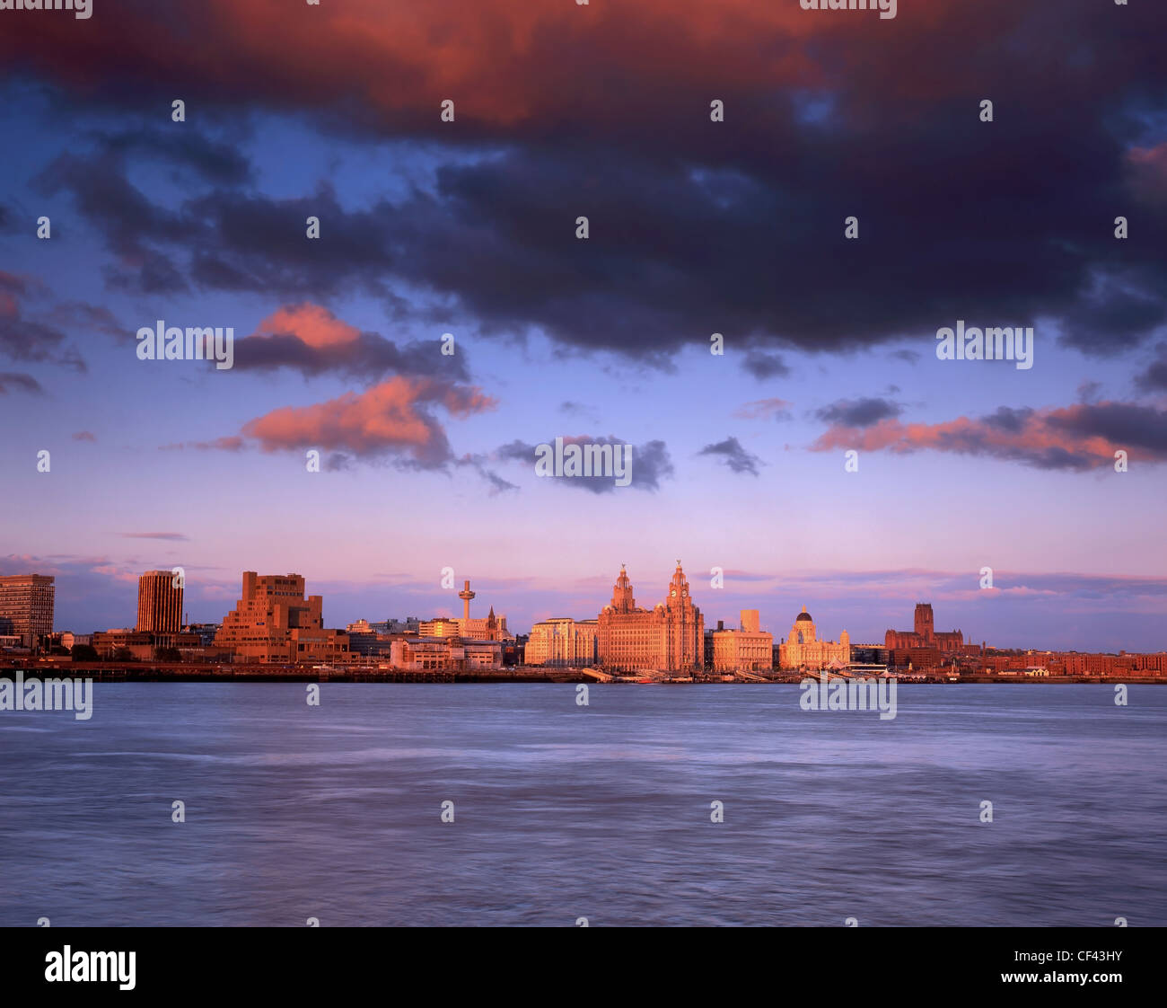 View across the River Mersey towards the Three Graces on the Liverpool waterfront at sunset. - Stock Image