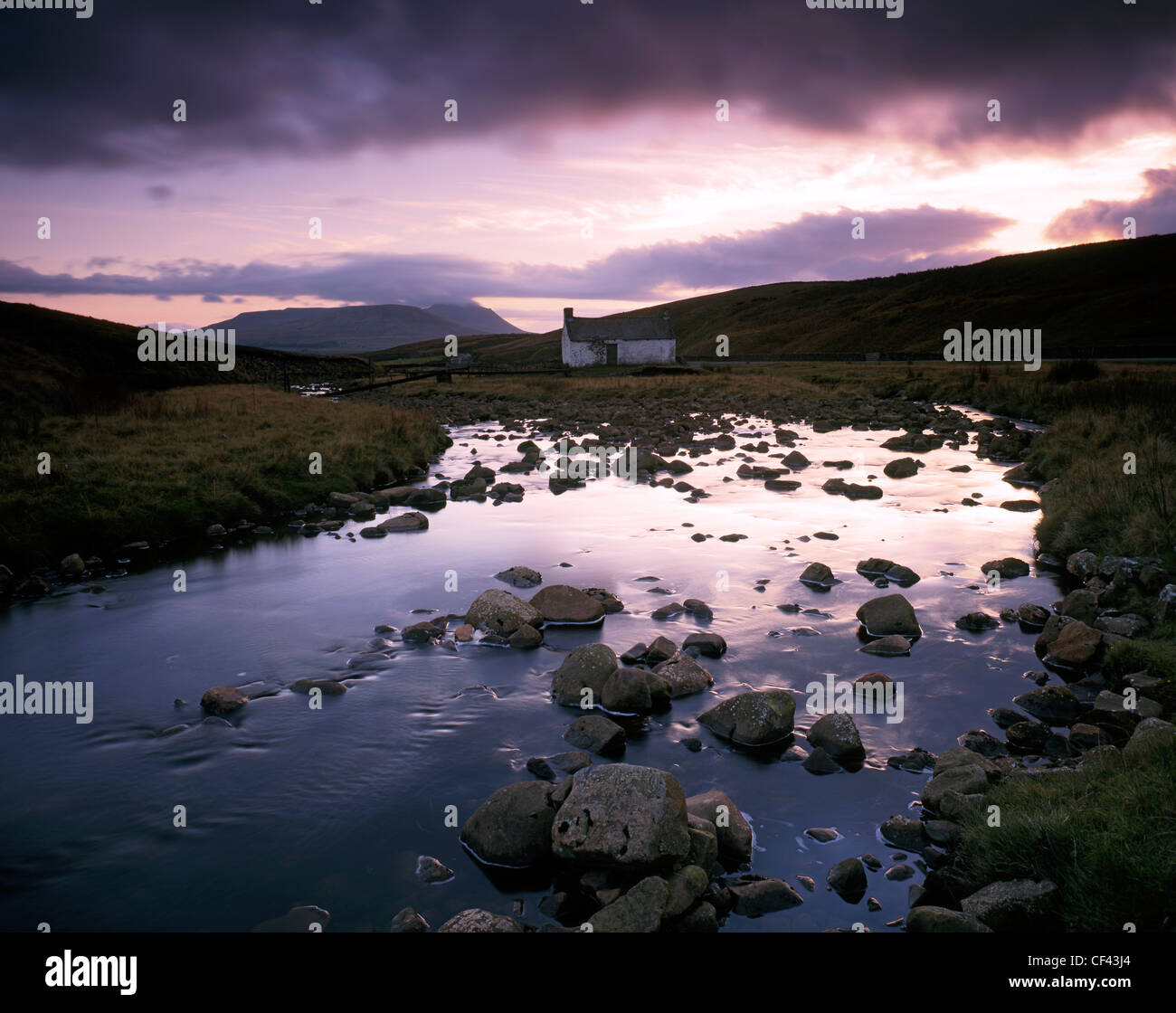 View along the River Ribble towards the (Yorkshire) Three Peaks as dusk descends. - Stock Image