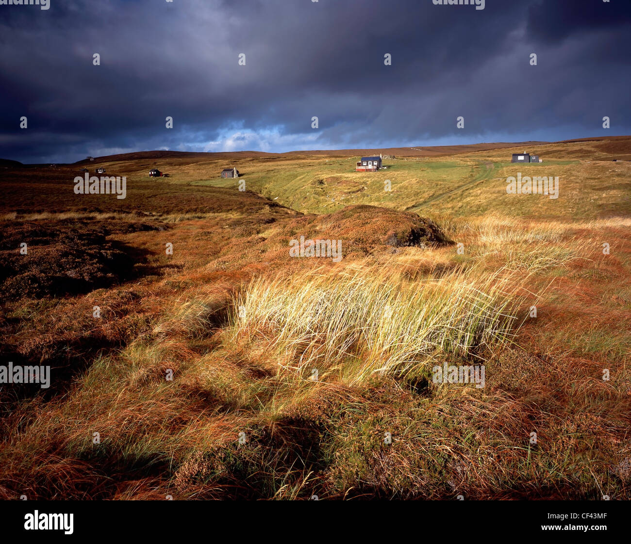 View across rugged moorland towards a scattered row of crofter's cottages on the Isle of Lewis. - Stock Image