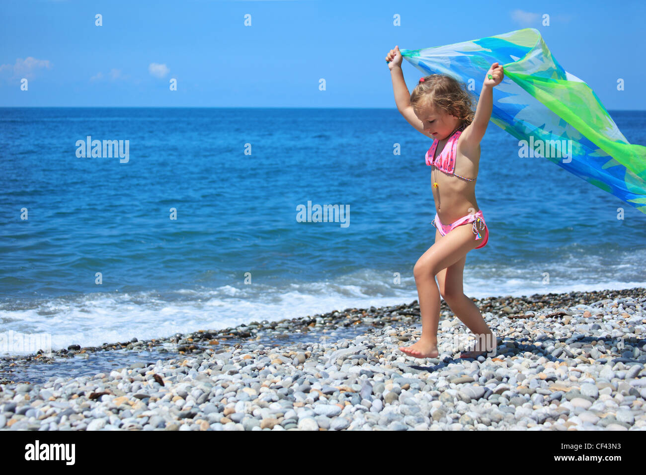 pretty little girl with fabric on stony seacoast, lifted hands upwards - Stock Image