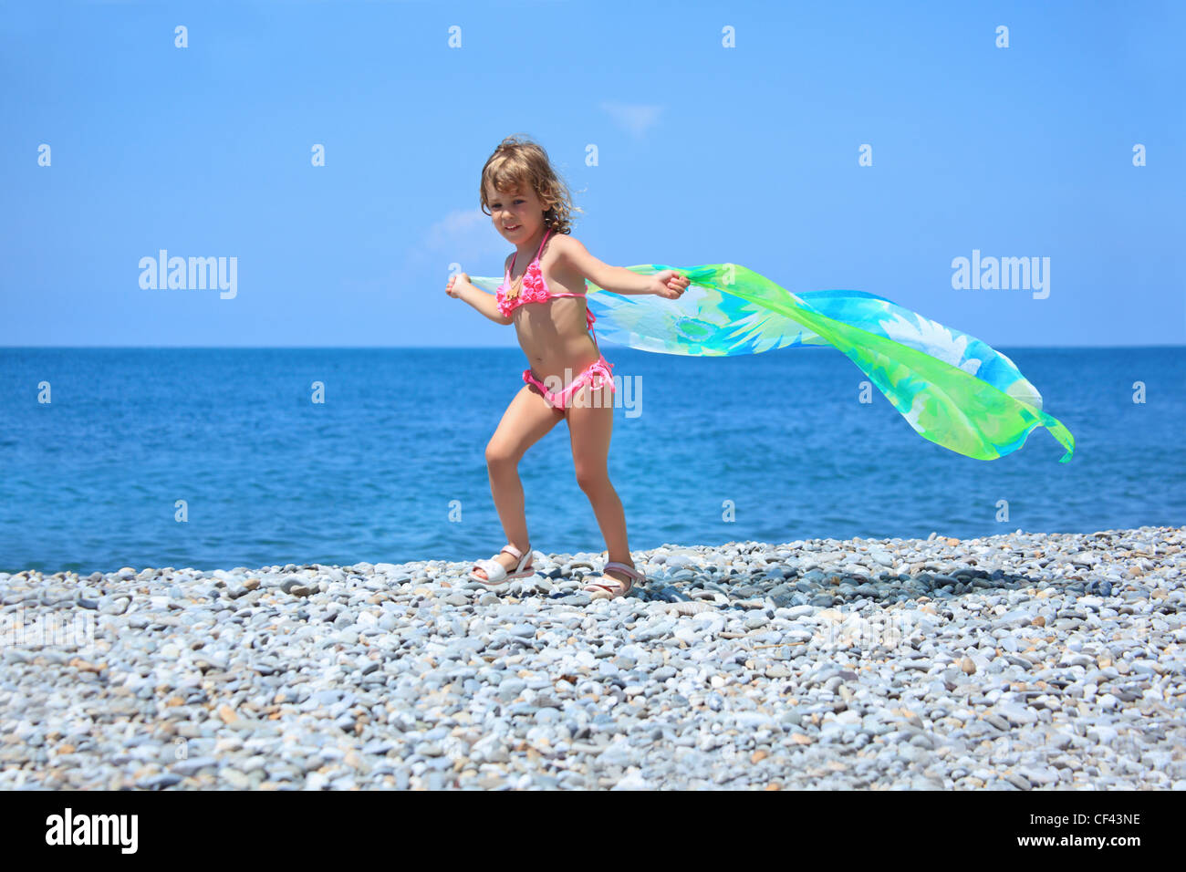 pretty little girl with fabric on stony seacoast - Stock Image