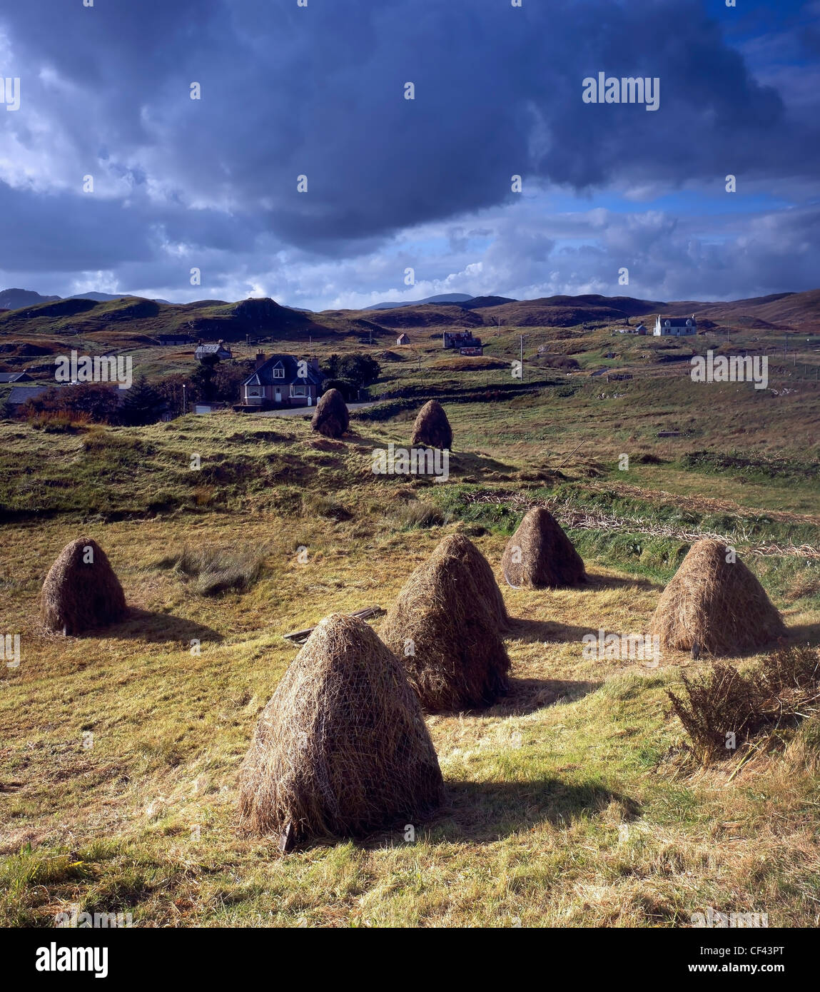 View over traditional, hand gathered hay bales towards the scattered community of Lacasaidh on the Isle of Lewis. Stock Photo