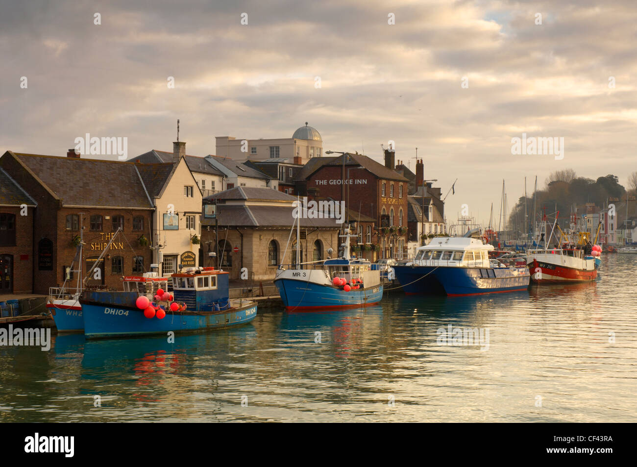 Traditional fishing trawlers moored at Weymouth old harbour. - Stock Image
