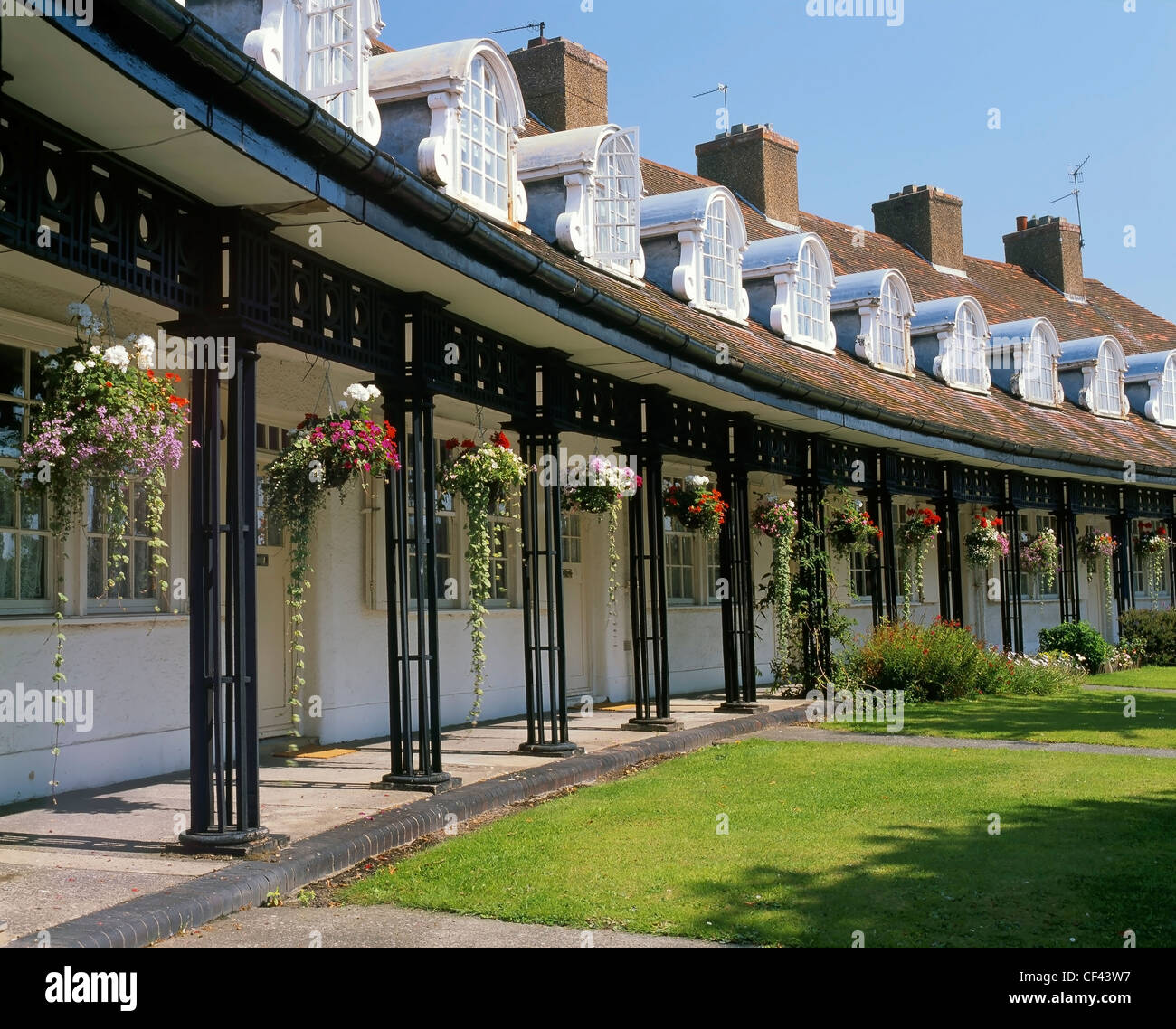 Hanging flower baskets outside cottages in Port Sunlight. The houses were originally built for employees of Lever - Stock Image