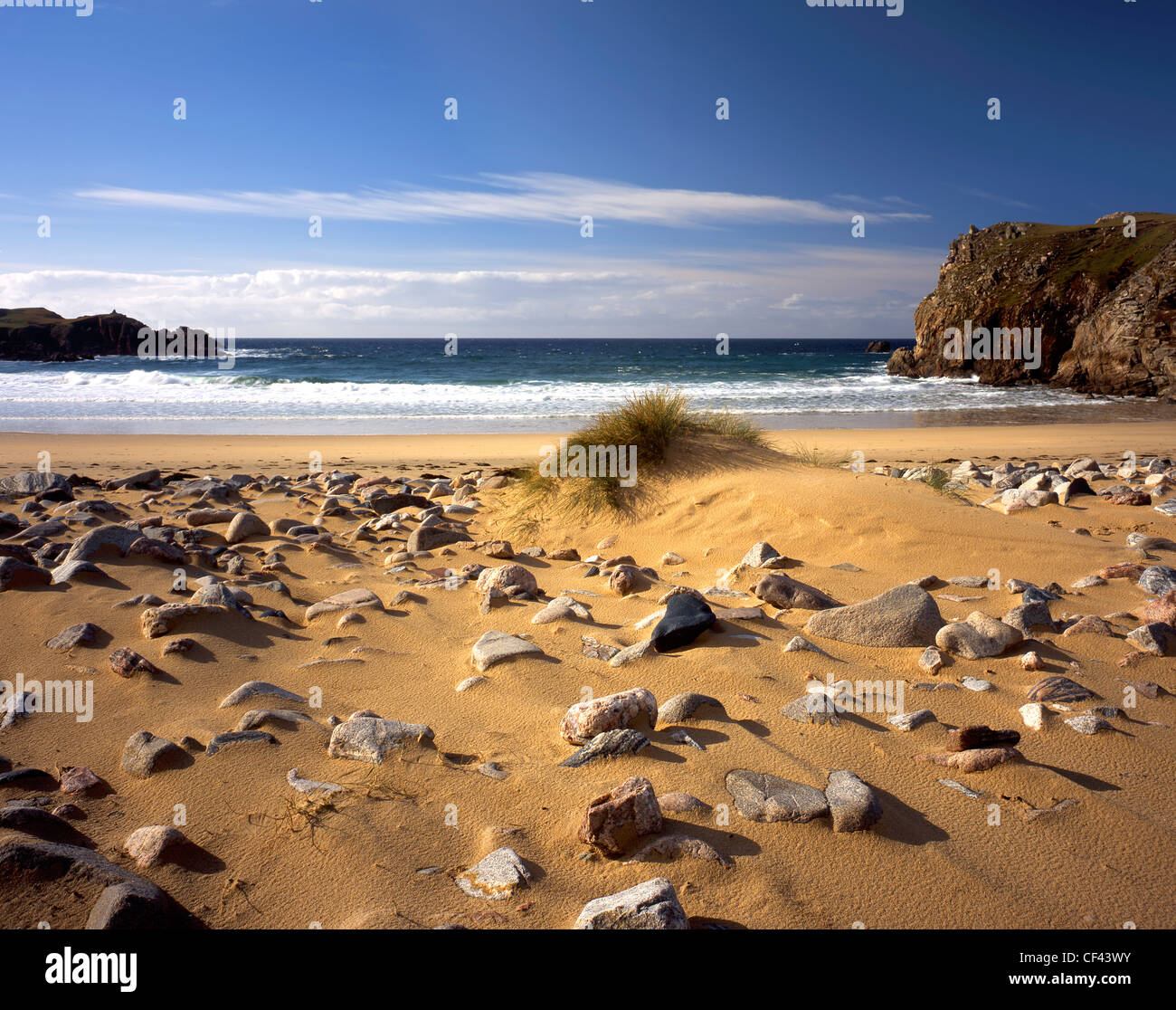 View out to the Atlantic Ocean from a remote rock covered sandy beach on the west coast of the Isle of Lewis. Stock Photo