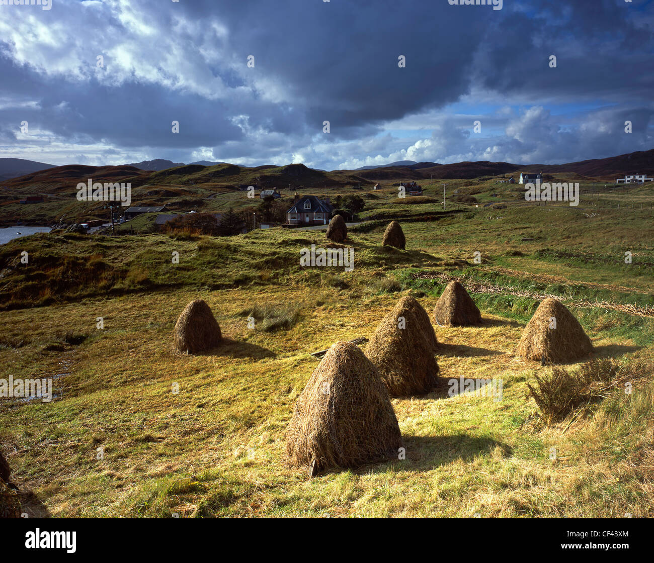 View over traditional hand built haystacks in a field towards the remote village of Tarbert on the Isle of Harris. Stock Photo