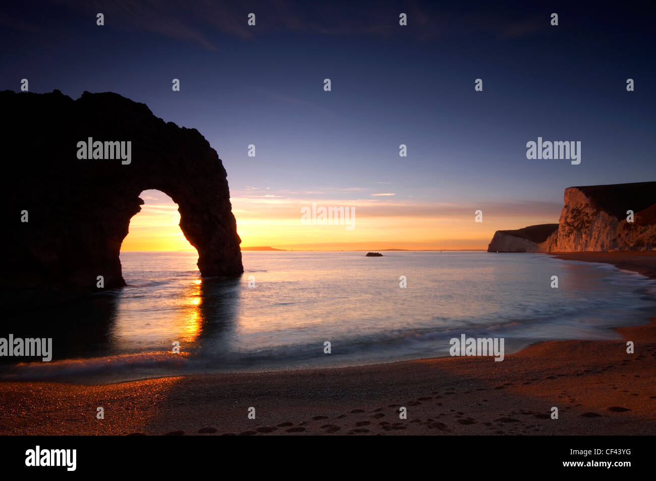 Sunset behind the arch of Durdle Door on the jurassic coast. - Stock Image
