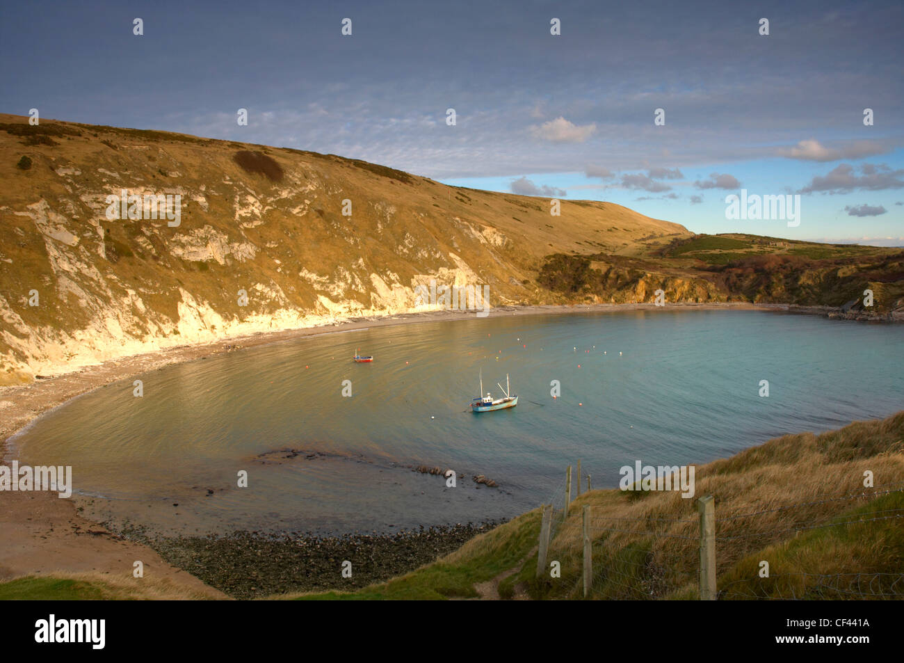 A fishing trawler anchored in Lulworth Cove on a bright winter day. - Stock Image
