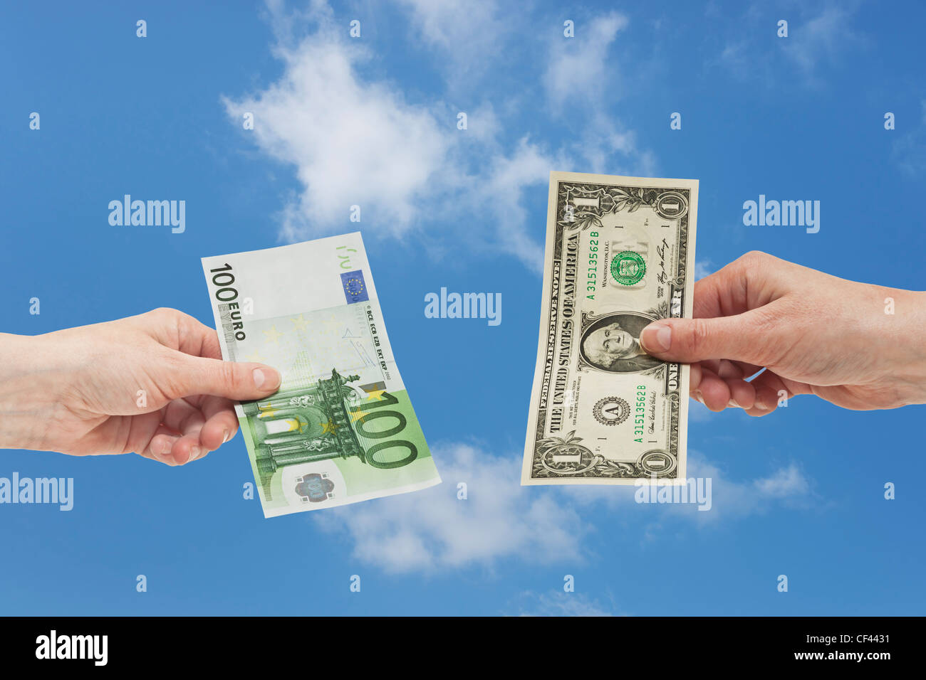 One 1 U.S. Dollar bill is held in the hand. At the other side a 100 Euro bill is held in the hand. Sky is in the - Stock Image