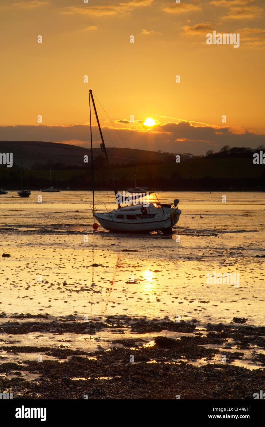 Sunset over the estuary and a lone yacht at low tide at Millbrook. - Stock Image