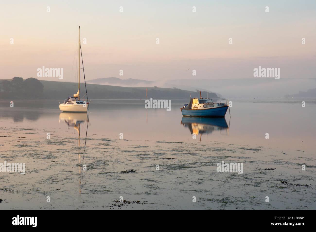 Misty dawn light on the Kingsbridge estuary illuminating small dinghys and fishing boats. - Stock Image