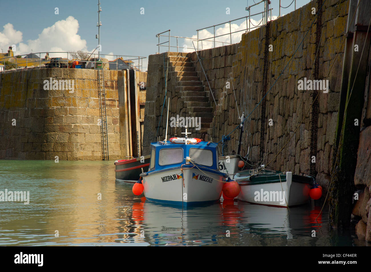 Small fishing boats moored alongside the harbour wall at Mousehole. - Stock Image