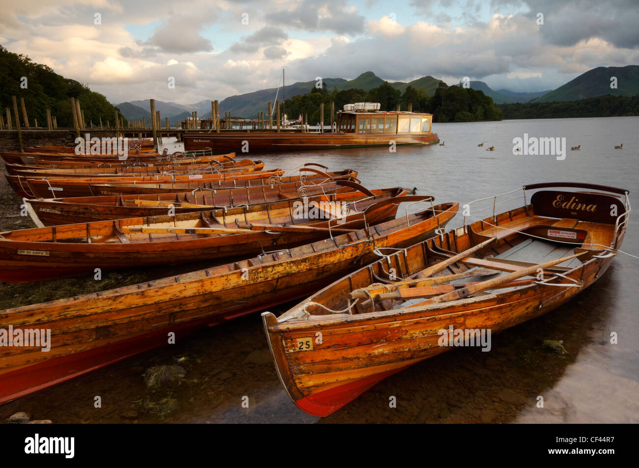 Sunset over rowing boats beached at Derwentwater landing stage. - Stock Image