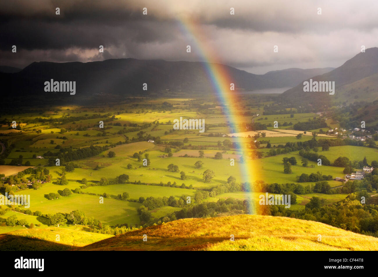 Dawn rainbow appears over Keswick and Bassenthwaite lake from Latrigg viewpoint. - Stock Image