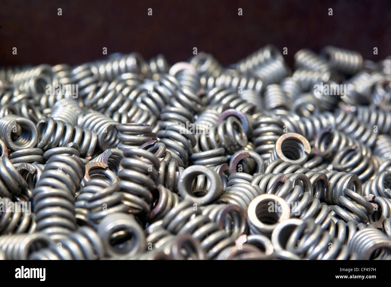 Many chamfered compression springs in a box - Stock Image