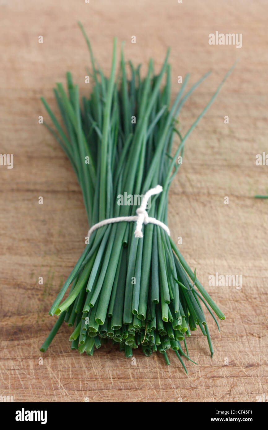 Chives on a wooden surface - Stock Image
